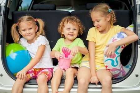 travel family: tres ni�os felices en el coche