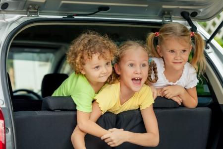 carritos de juguete: tres ni�os felices en el coche