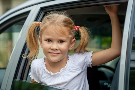 cars on road: little girl sitting in the car Stock Photo
