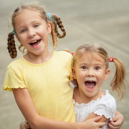 kids having fun: two happy sisters