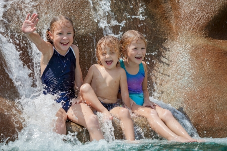 man waterfalls: three happy kids sitting near the pool in the waterpark