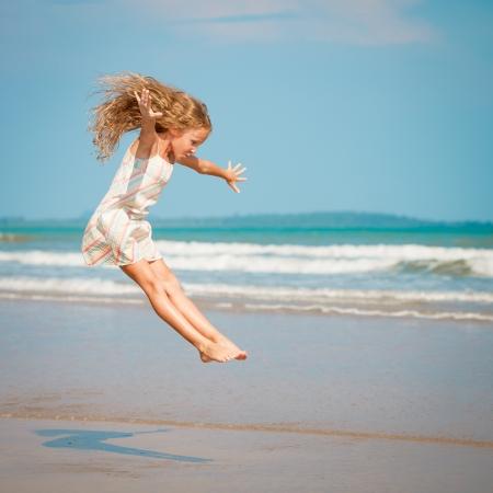 klein meisje op strand: vliegende sprong strand meisje op blauwe overzeese kust in de zomer vakantie