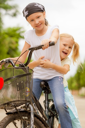 2 persons only: two happy children on a bicycle Stock Photo