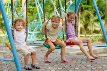 kids playing outside: happy little girls and boy on a swing
