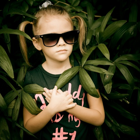beautiful little girl in sunglasses and a black T-shirt that says  Daddy