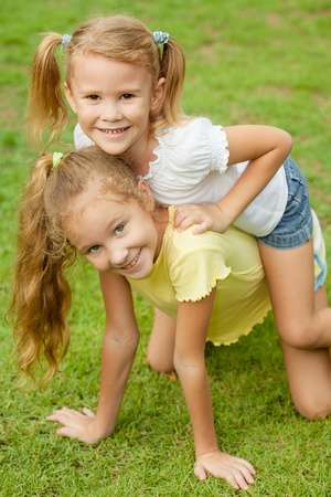 two happy little girls in the park photo