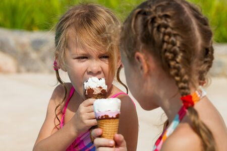 two little girls eating ice cream near the pool photo
