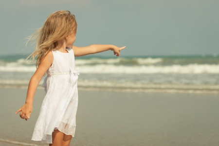 happy little  girl standing  on the  beach and showing at the sea photo