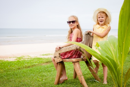 two happy little girls near the beach photo