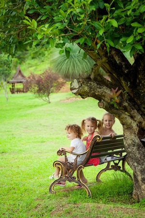 happy kids sitting on the bench near the tree photo