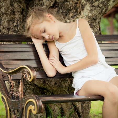 portrait of a sad child  sitting on a bench in the park under the tree photo