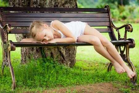 fille triste: Portrait d'un enfant triste couché sur un banc dans le parc sous l'arbre