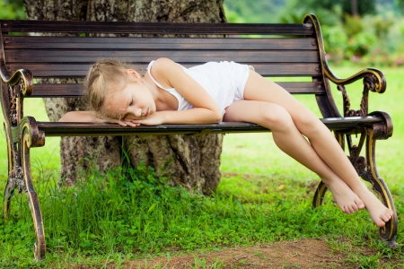 sad faces: portrait of a sad child  lying on a bench in the park under the tree Stock Photo