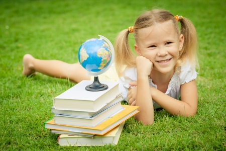 little girl with books lying on the grass photo