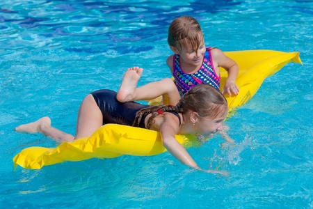 two happy little girls playing  in the pool on the airbed photo