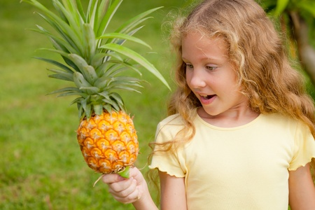 happy little girl holding in hands  a pineapple photo