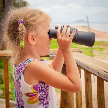 little girl on the beach looking at the sky through binoculars photo