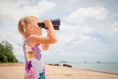 little girl on the beach looking at the sky through binoculars