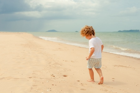 Little boy playing on the beach  photo
