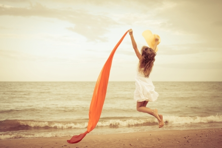 day time: flying jumping beach girl at blue sea shore in summer vacation in the day time