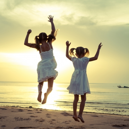 Happy children jumping on the beach on the dawn time photo