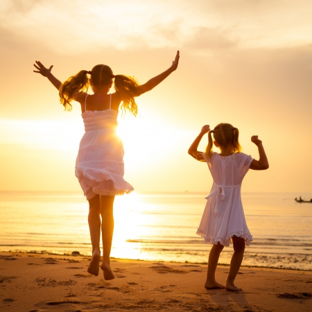 Felices los niños saltando en la playa en el momento del amanecer Foto de archivo