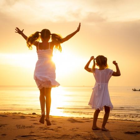 jumping: Felices los niños saltando en la playa en el momento del amanecer