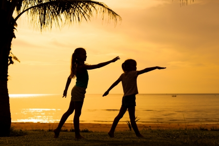 Happy children playing on the beach on the dawn time photo