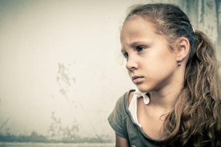 misery: portrait of a sad girl on a background white wall Stock Photo
