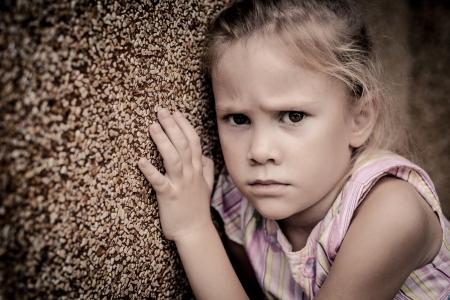 壁の近くに座って悲しい少女の肖像画