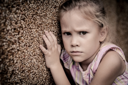 portrait of a sad little girl sitting near the wall Stock Photo