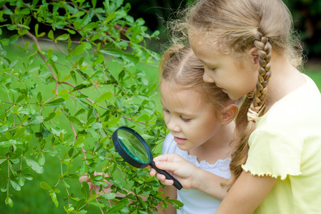 Two little girls with magnifying glass outdoors in the day time photo