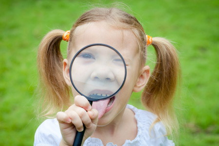 one little girl with magnifying glass outdoors in the day time photo