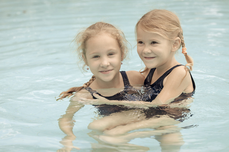 two happy little girls playing in the swimming pool photo