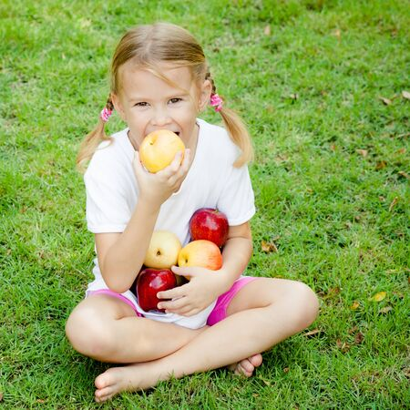 little girl sitting on the grass and holding apples photo
