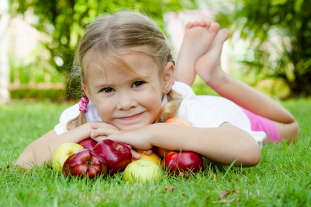 lying on grass: little girl lying on the grass and holding apples Stock Photo