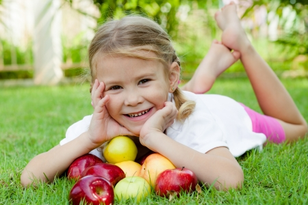 little girl lying on the grass and holding apples photo
