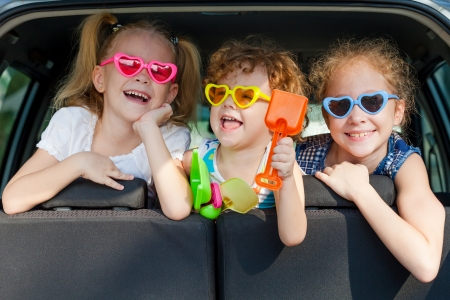 summer girl: two little girls  and boy sitting in the car  Stock Photo