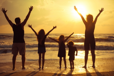 healthy women: Happy family standing on the beach on the dawn time