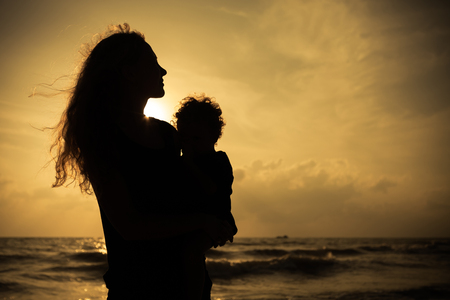 mother nature: Mother and little son silhouettes on beach at sunset