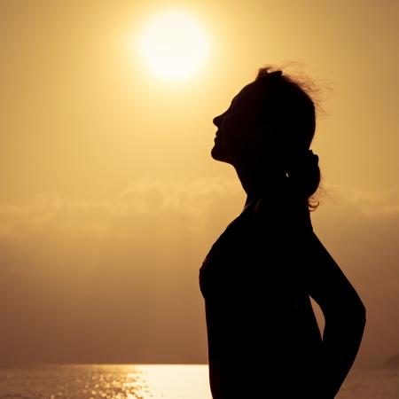mujer sola: Silueta de la mujer que estaba en la playa durante el hermoso atardecer Foto de archivo