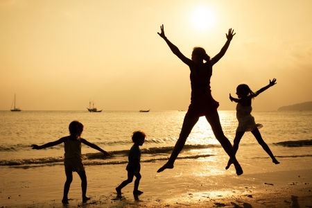 Happy family jumping on the beach on the sunrise time photo