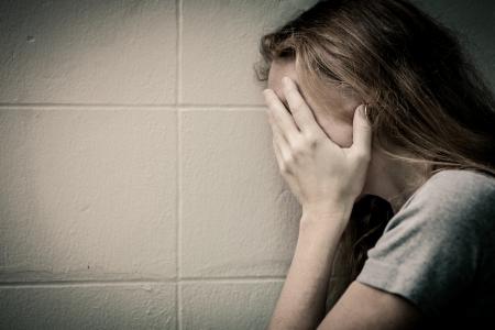 perdonar: una triste mujer sentada en el suelo cerca de la pared y sosteniendo su cabeza en sus manos