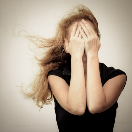 caras tristes: una triste mujer de pie cerca de una pared y sosteniendo su cabeza en sus manos