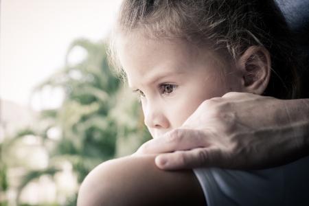 portret van een droevig meisje zit in de buurt van het raam