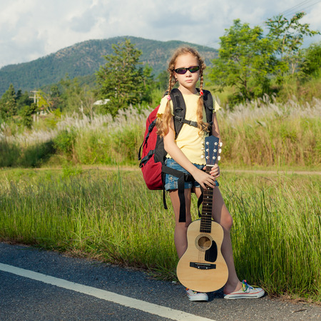 one girl with backpack and guitar  walking on the road photo