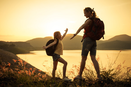 M�re et fille en regardant le coucher de soleil sur le lac photo
