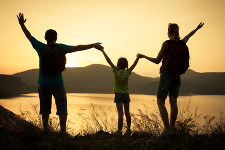 Happy family watching the sunset on the lake photo