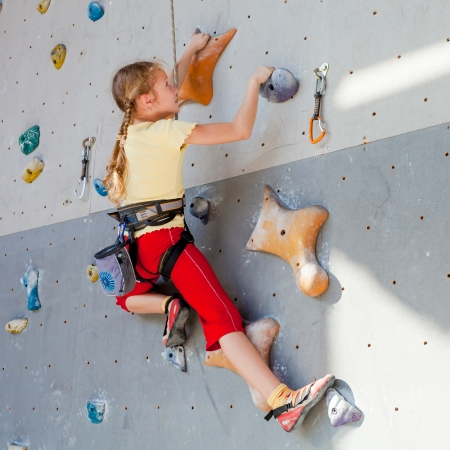 to climb: teenager climbing a rock wall Stock Photo