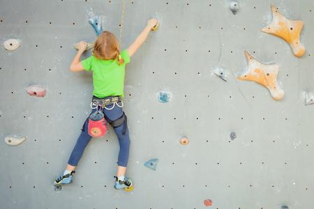 climbing: Little Girl Climbing Rock Wall